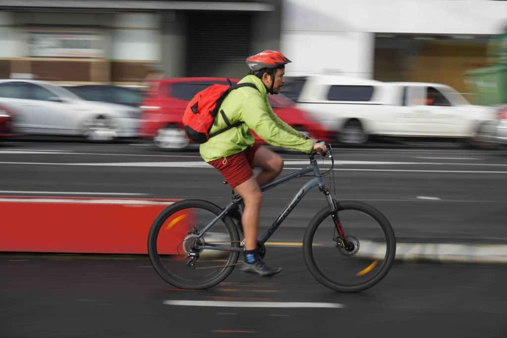 Cycling Knee Pain Explained - A man cycling his bicycle on the street.