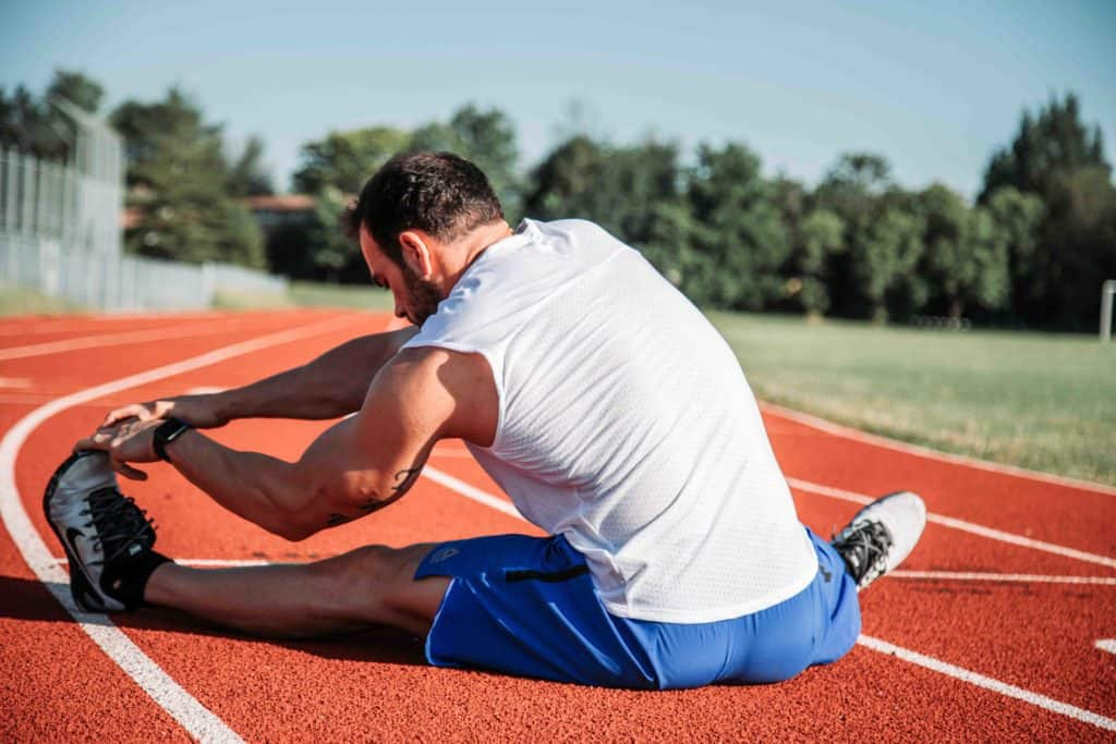 Cycling Knee Pain Explained - A man doing leg and knee stretching before exercising.
