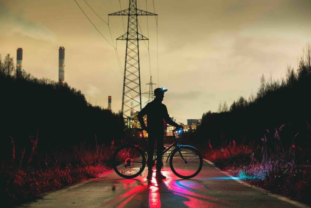 Cyclist with lights on his head and bicycle at night. Bicycle Helmet Laws by US State